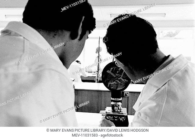 Schoolboy and teacher working at a microscope in the science laboratory with a skeleton in the distance at Atlantic College (United World College of the...