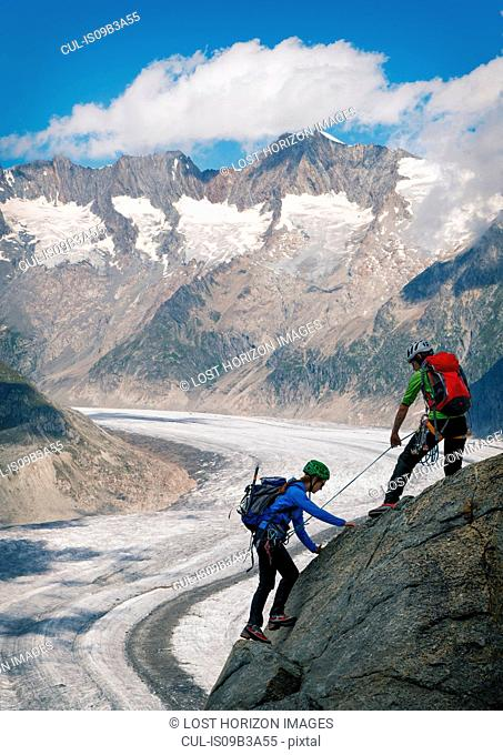 Couple climbing up ridge over Aletsch Glacier, Canton Wallis, Switzerland