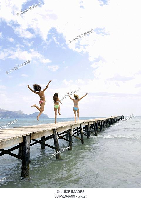Three women jumping on pier