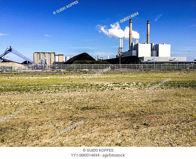 Maasvlakte, Rotterdam, Netherlands. The E.ON owned and cole fired electricity plant on the Maasvlakte, with mountains of cole stored at the left of the boiler...