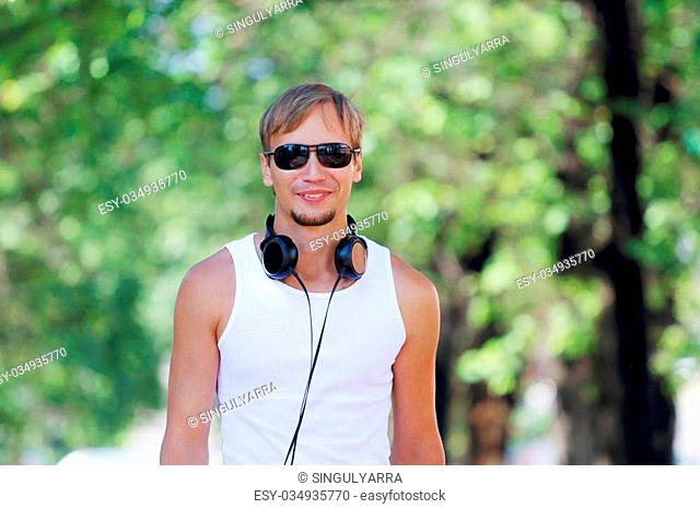 Smiling man in sunglasses and headphones on alley with green trees at summer day