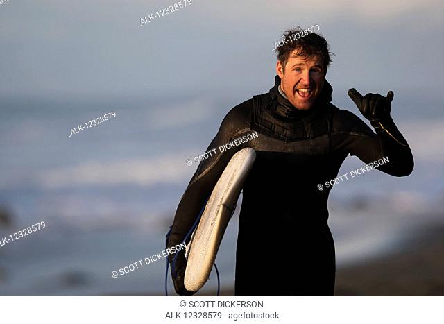 Enthusiastic surfer holding a surfboard along coast Southeast Alaska; Yakutat, Alaska, United States of America