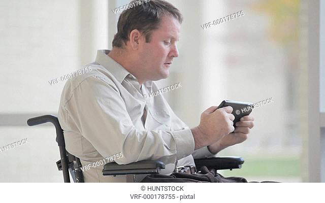 Quadriplegic man with spinal cord injury struggling with a tablet in his hands
