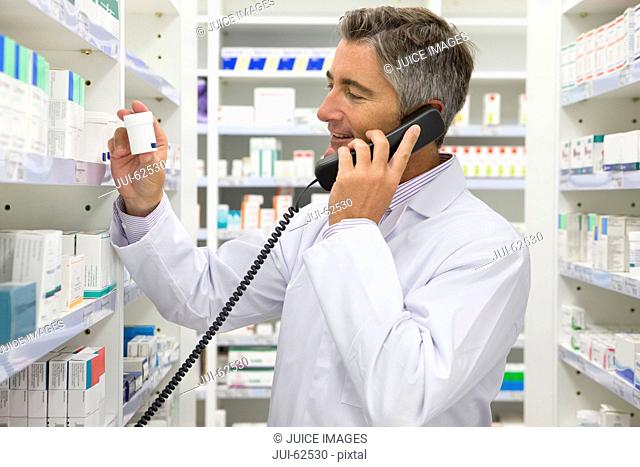 Pharmacist talking on phone and holding medication in pharmacy