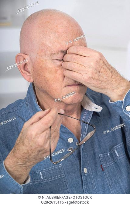 Senior man with eyes shut, rubbing his eyes because of fatigue or headache, and holding his glasses in one hand