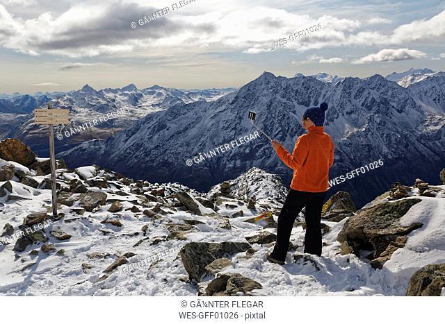 Austria, Tyrol, Oetztal, Soelden, woman with selfie stick at Gaislachkogel