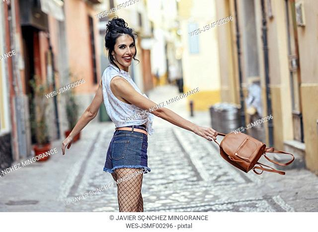 Fashionable woman with small backpack in the city