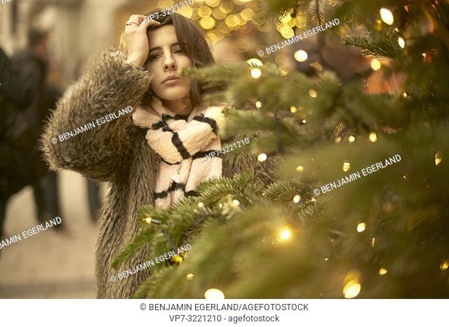 portrait of pensive young woman behind lights of Christmas tree, wearing fashionable winter clothes, in city Munich, Germany