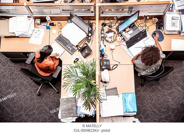 Overhead view of two businesswomen at office desk