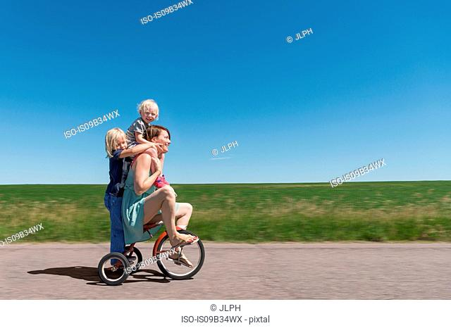 Side view of mother and children riding tricycle in rural area