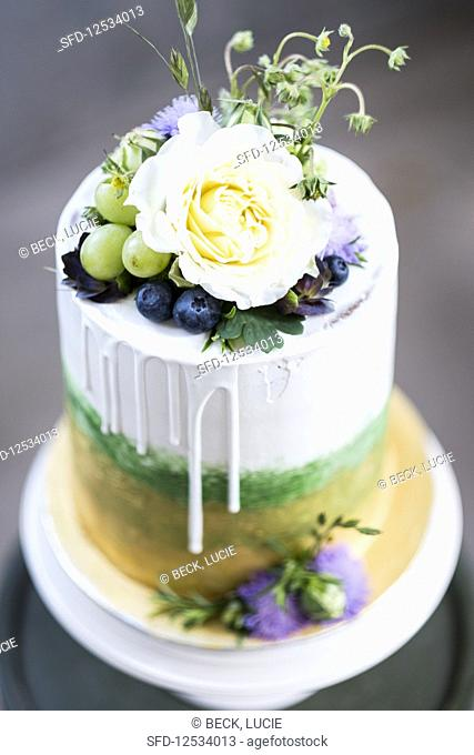 A layered cake with gold, green, grapes and flowers
