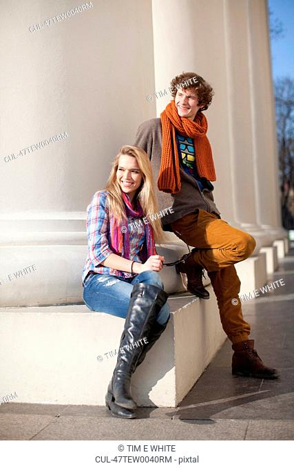 Couple sitting by pillars on building