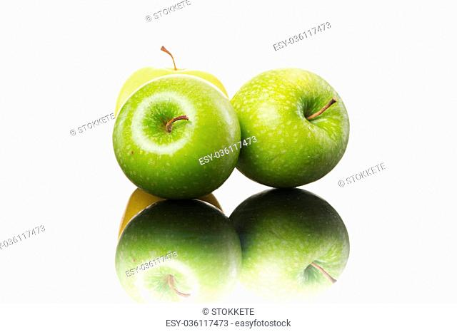 Juicy yellow and green shiny apples on white background