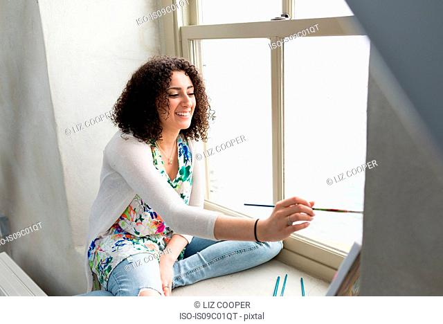 Young female painter painting canvas on studio windowsill