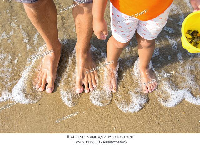 Two pairs of legs adult and child washed waves of the sea, the child also holds vederochko with shells in their hands