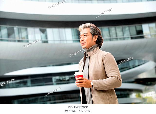 Business man holding a coffee cup to go to work