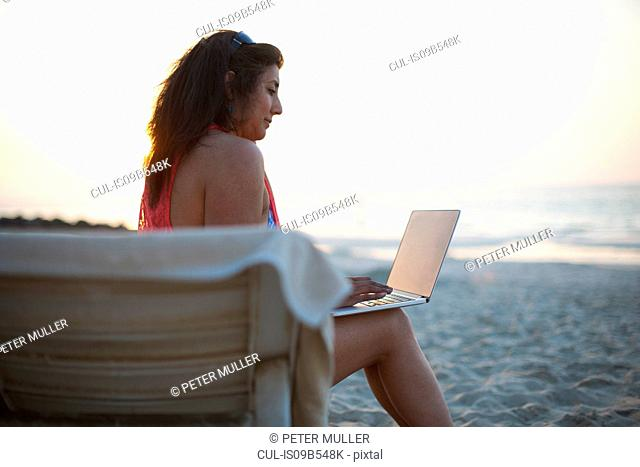 Mature woman sitting on beach sun lounger looking at laptop, Dubai, United Arab Emirates
