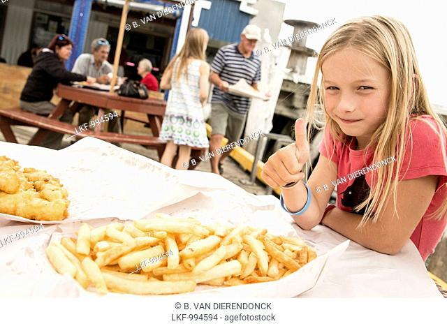 A girl with fish and chips at Tauranga, North Island, New Zealand