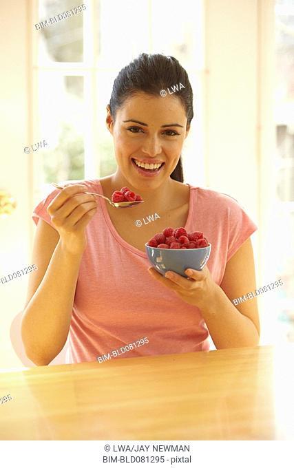 Hispanic woman eating bowl of raspberries