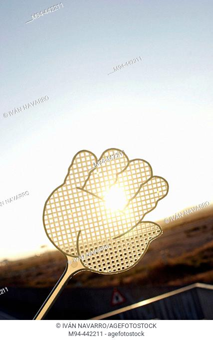 Hand-shaped fly swat covering sun
