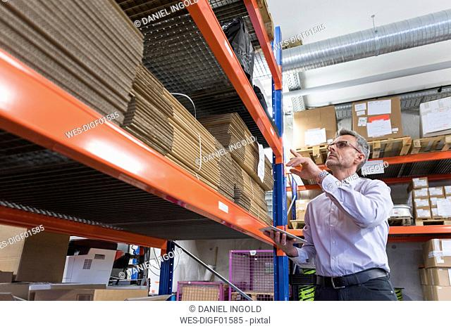Businessman with tablet in factory hall