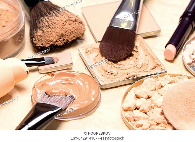 Foundation, powder, concealer with make-up brushes on crumpled paper. Corrective makeup products and accessories close-up, selective focus