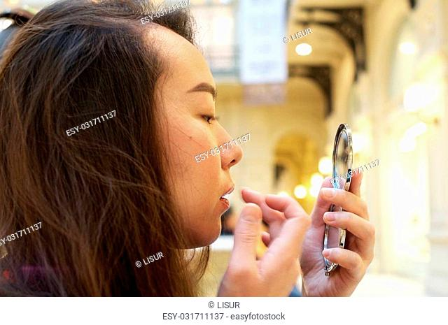 Girl putting make-up on lips looking in handheld mirror
