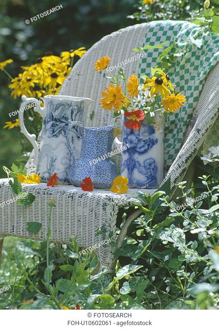 Still-life of blue+white china jugs on old white Lloyd Loom chair in garden