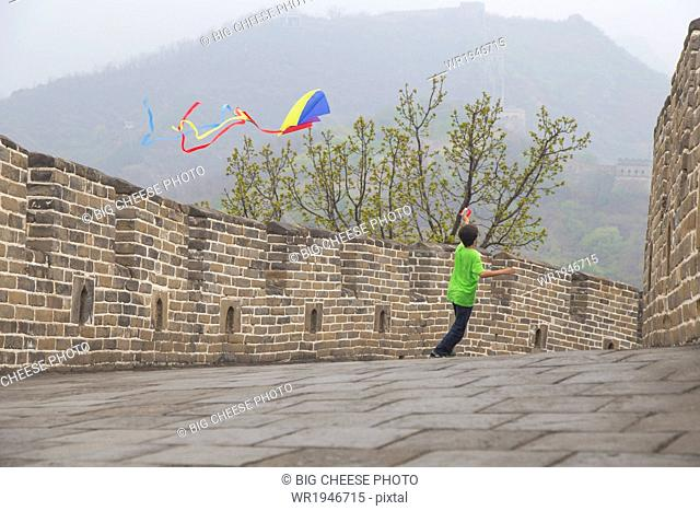Boy running with a kite on the Great Wall of China, at Mutianyu, Huairou, China