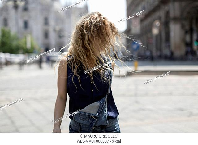 Italy, Milan, young woman tossing her hair