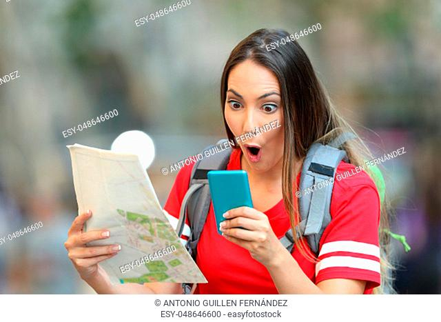 Surprised teen tourist holding a map and reading online content in a smart phone on the street