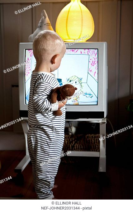 Baby boy standing in front of TV