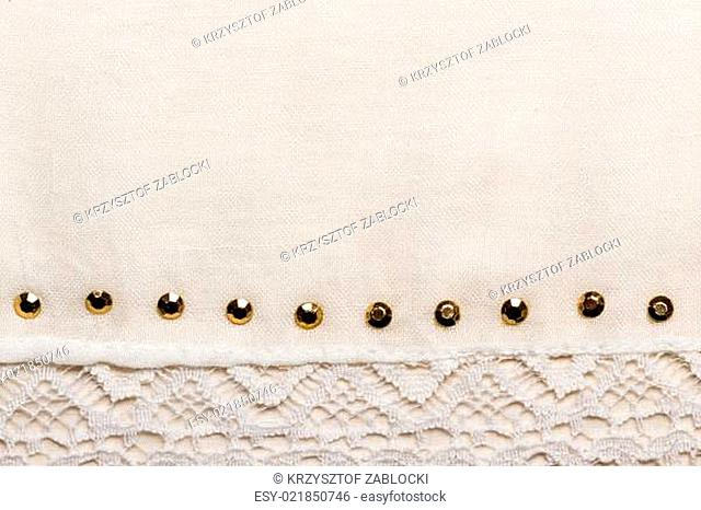 White cloth background with lace and studs