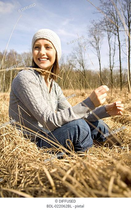 portrait of young woman in autumn sitting on meadow