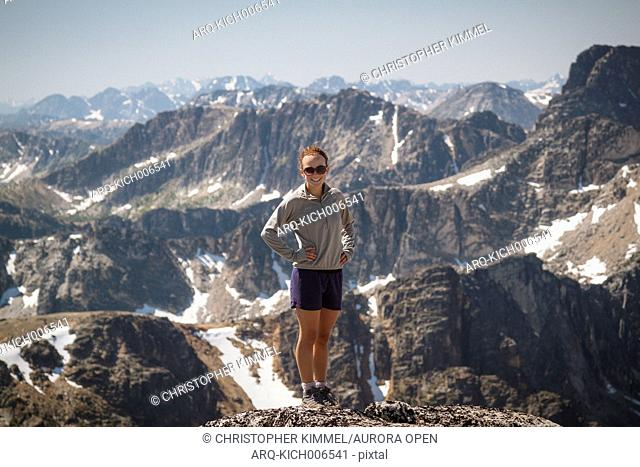 Portrait of a fit young woman standing on the summit of Lakeview Mountain in Cathedral Lakes Provincial Park, British Columbia, Canada