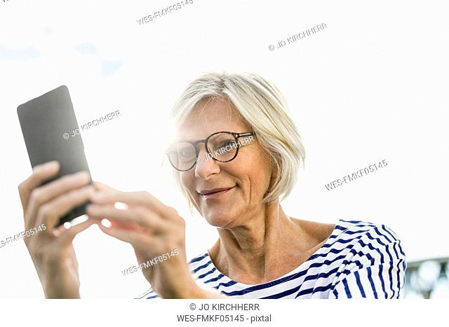 Smiling senior woman using cell phone outdoors