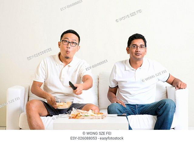 Men sitting on couch watching television, Asian people friendship at home