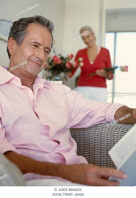 Mature man reading as wife arranges flowers in the background
