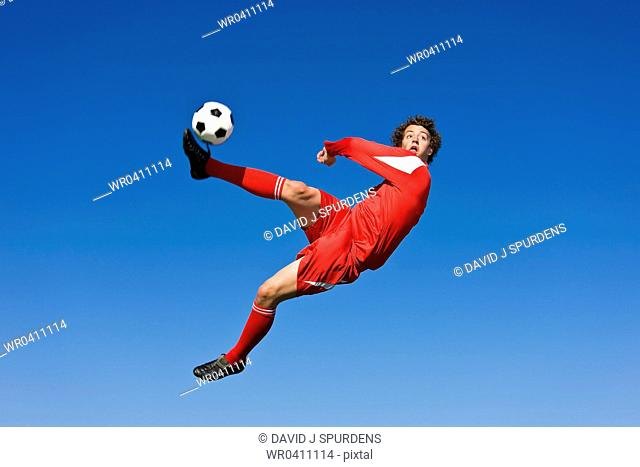 A soccer player volleys the ball