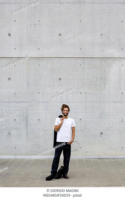 Smiling young businessman with dreadlocks standing in front of concrete wall