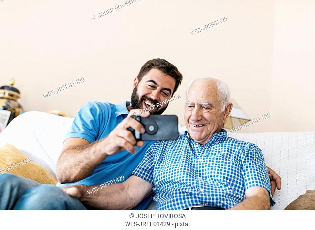 Portrait of adult grandson and his grandfather taking selfie with smartphone at home