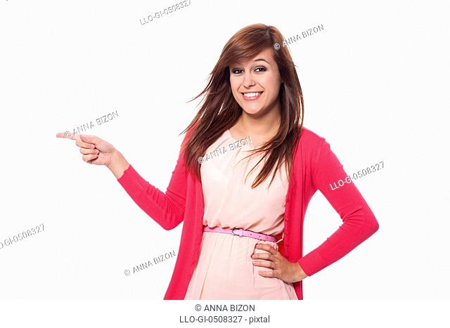 Beautiful woman in pink clothes pointing at copy space, Debica, Poland