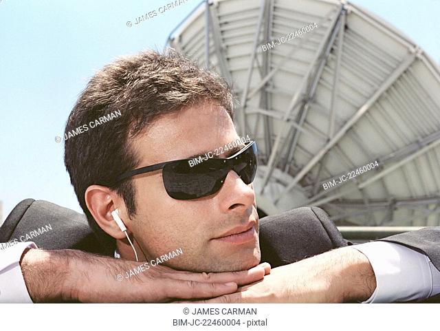 Hispanic man wearing earbuds next to satellite dish