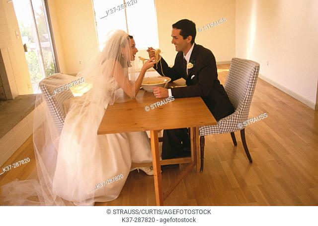 Bride and groom sharing a bowl of spaghetti sitting in new home with no furniture