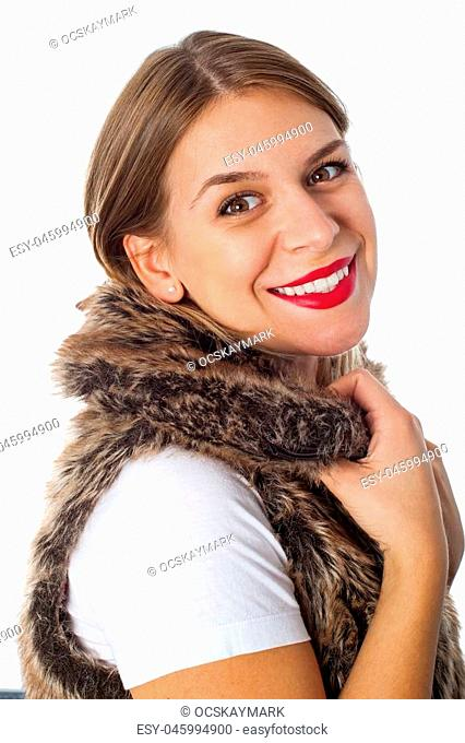 Attractive young woman wearing natural fur vest, smiling at the camera on isolated background