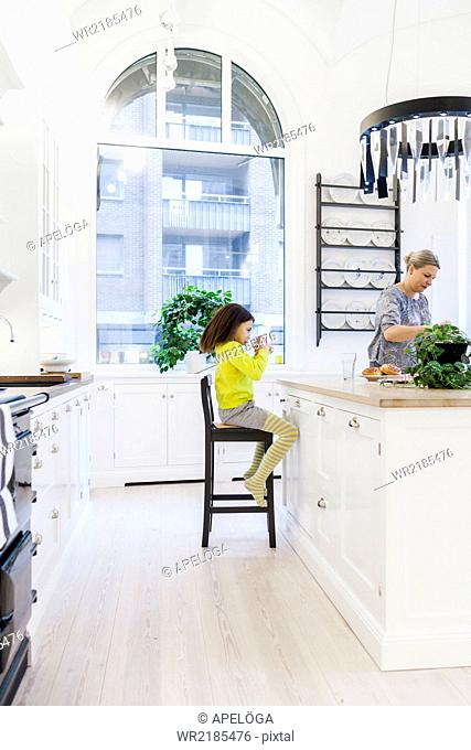 Girl drinking juice while mother cooking in kitchen
