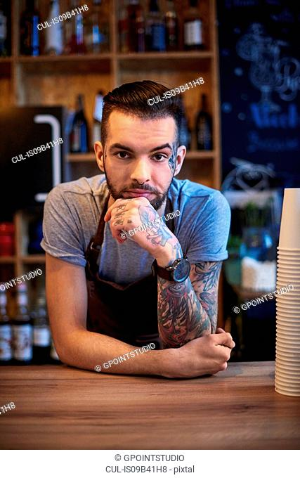 Barista leaning on counter day-dreaming