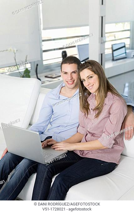 Couple with laptop at home smiling at camera