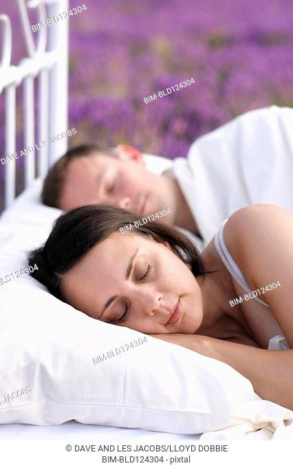 Couple sleeping in bed in lavender field
