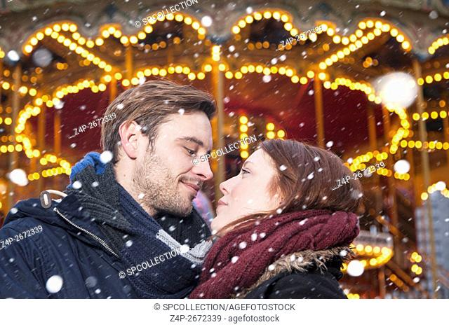 Couple on christmas market with snowflakes